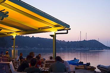 A waterside taverna at dusk in Lakka, Paxos, Ionian Islands, Greek Islands, Greece, Europe