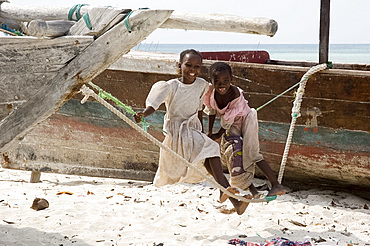 Two little girls on a makeshift swing on the beach at Nungwi, Zanzibar, Tanzania, East Africa, Africa