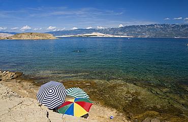 Beach umbrellas by the sea at San Marino, island of Rab, Kvarner region, Croatia, Europe