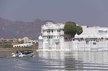 A small boat heading toward the Lake Palace Hotel on Lake Pichola in Udaipur, Rajasthan, India, Asia