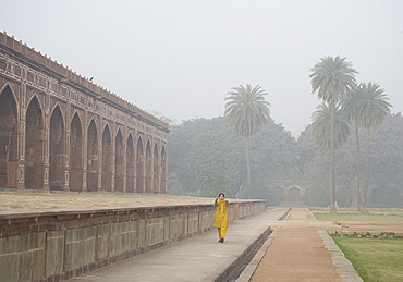 A woman exercising early in the morning in the garden at Humayun's Tomb, New Delhi, India, Asia