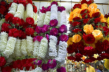 Garlands of colourful artificial flowers for sale in the market in Old Delhi, India, Asia