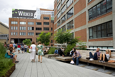 People sitting on wooden lounge chairs and strolling on the newly created High Line park area on an old rail line in lower Manhattan, New York City, New York State, United States of America, North America