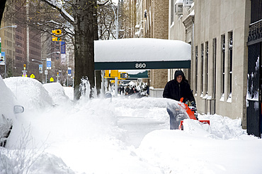 A man using a snow blower on Park Avenue after a blizzard in New York City, New York State, United States of America, North America