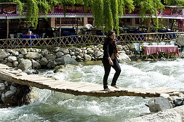 Crossing over a raging river on a precarious wooden slatted bridge in Setti Fatma, Ourika Valley, Morocco, North Africa, Africa