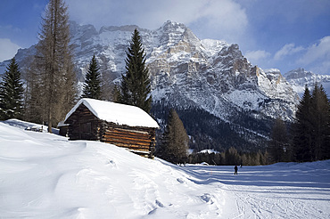 A snow covered wooden barn at the Alta Badia ski resort with Lavarella and Contourines mountains, Corvara, The Dolomites, South Tyrol, Italy, Europe