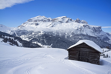 A snow covered wooden barn at the Alta Badia ski resort with Lavarella and Contourines mountains in the background, Dolomites, South Tyrol, Italy, Europe
