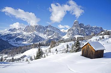 Mounts Lavarella, Conturines and Sasongher behind a snow covered wooden barn at the Alta Badia ski resort, Corvara, Dolomites, South Tyroll, Italy, Europe