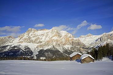 Mounts Lavarella and Conturines behind a pair of snow covered wooden barns at the Alta Badia ski resort near Corvara, Dolomites, South Tyrol, Italy, Europe