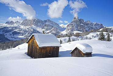 Mounts Lavarella, Conturines and Sasongher behind snow covered wooden barns at the Alta Badia ski resort near Corvara, Dolomites, South Tyrol, Italy, Europe