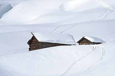 Two old wooden barns surrounded by deep snow and ski tracks in the Dolomites, South Tyrol, Italy, Europe