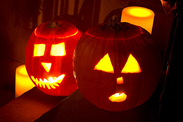 Two jack o'lanterns on the steps of a New York brownstone on Halloween night, Manhattan, New York City, United States of America, North America