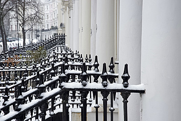 Snow covered iron railings in front of houses in the Notting Hill area of London, England, United Kingdom, Europe