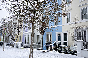 Pastel coloured houses on a snowy day in Elgin Crescent in the Notting Hill area of London, England, United Kingdom, Europe