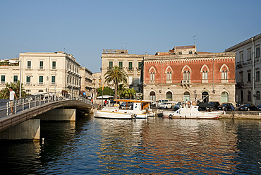 A deep red Venetian style building in the harbour in Ortigia, Syracuse, Sicily, Italy, Mediterranean, Europe