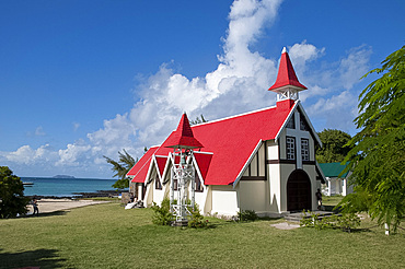A newly wed couple posing for photos outside the red roofed church at Cap Malheureux on the northwest coast of Mauritius, Indian Ocean, Africa