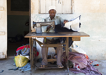 A local man making clothing with an old Singer Sewing Machine in Pangani, Tanzania, East Africa, Africa