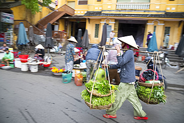 A woman walking through the market with heavy baskets of vegetables in Hoi An, Quang Nam Province, Vietnam, Indochina, Southeast Asia, Asia