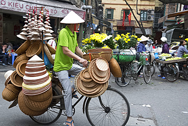 A man selling Vietnamese Conical straw hats and baskets from his bicycle in the Old Quarter, Hanoi, Vietnam, Indochina, Southeast Asia, Asia