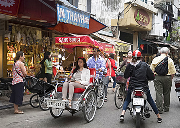 A tourist in a cyclo on a busy street in the Old Quarter, Hanoi, Vietnam, Indochina, Southeast Asia, Asia