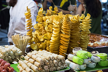 Chips and rolls on skewers at a night market in the Old Quarter of Hanoi, Vietnam, Indochina, Southeast Asia, Asia