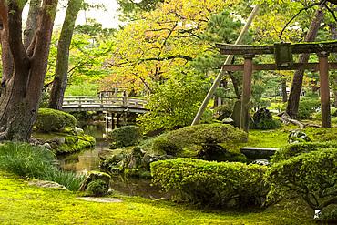 Hanambashi Bridge and a stone gate surrounded by autumn foliage in the Kenrokuen Garden, Kanazawa, Ishigawa, Japan, Asia
