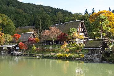 Autumn foliage and traditonal thatched buildings around a lake at Hida Folk Village, Hida No Sato, Takayama, Honshu, Japan, Asia