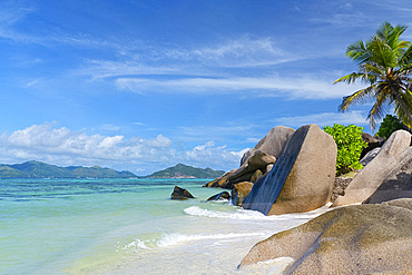 Waves swirling around large granite boulders and palm trees on Anse Source d'Argent, La Digue, Seychelles, Indian Ocean, Africa