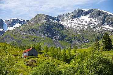 A wooden barn on a hillside below the Frudalsbreen Glacier, Vestlandet, Norway, Scandinavia, Europe