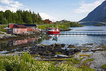 A fishing boat and dock houses near Kakern Bridge, Ramberg, Lofoten Islands, Norway, Europe