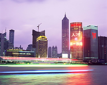 View across river at dusk to the new Pudong district skyline, Huangpu River, Shanghai, China, Asia