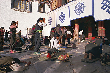 Tibetan Buddhist pilgrims prostrating at the Jokhang temple, Barkhor, Lhasa, Tibet, China, Asia
