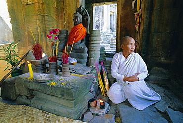 Buddhist nun meditating in the Bayon Temple, at Angkor, Siem Reap, Cambodia