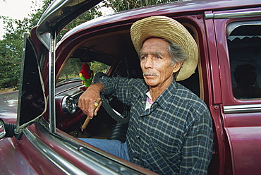 A man sitting in a 1950's American car, Pinar Del Rio Province, Cuba, West Indies, Caribbean, Central America