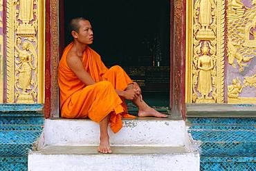 Monk sitting in temple doorway, Wat Xieng Thong, Luang Prabang, Laos