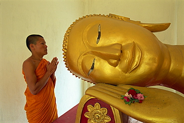 Novice monk and reclining Buddha, Wat Pha Baat Tai, Luang Prabang, Laos, Indochina, Southeast Asia, Asia