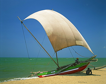 Fishermen in the shade of a sail on a fishing boat on the beach at Negombo, Sri Lanka, Asia