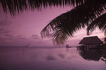 People in beach bar near the Moorings at sunset, Placencia, Belize, Central America