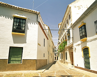 White walled houses on a narrow street in the village of Ecija, in the province of Seville, Andalucia, Spain, Europe