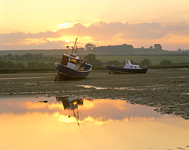 Fishing boat at sunset on the Aln estuary at low tide, Alnmouth, Northumberland, England, United Kingdom, Europe