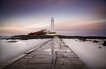 View along the tidal causeway to St. Mary's Island and St. Mary's Lighthouse at dusk, near Whitley Bay, Tyne and Wear, England, United Kingdom, Europe