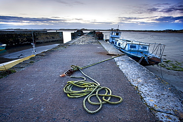 Beadnell Harbour at dusk showing old rope coiled on harbourside and dilapidated fishing boat, Beadnell, Northumberland, England, United Kingdom, Europe
