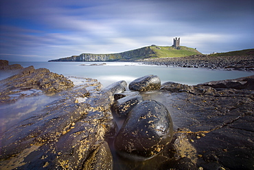 Dunstanburgh Castle bathed in afternoon sunlight with rocky coastline in foreground, Embleton Bay, near Alnwick, Northumberland, England, United Kingdom, Europe