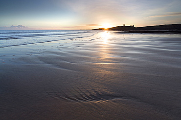 View over Embleton Beach at sunrise towards the silhouetted ruin of Dunstanburgh Castle in the distance, Embleton Bay, near Alnwick, Northumberland, England, United Kingdom, Europe