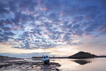 View towards Church Hill and the Aln Estuary during a stunning winter sunrise from the beach at low tide with a fishing boat in the foreground, Alnmouth, near Alnwick, Northumberland, England, United Kingdom, Europe