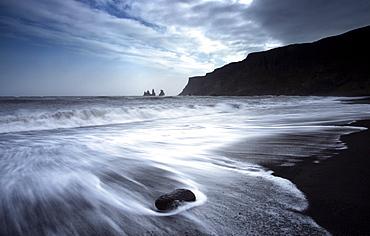 The rockstacks of Reynisdrangar from the black volcanic sand beach at Vik i Myrdal, South Iceland, Iceland, Polar Regions