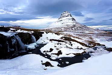 Kirkjufell (Church Mountain) covered in snow with a frozen river and waterfall in the foreground, near Grundarfjordur, Snaefellsnes Peninsula, Iceland, Polar Regions