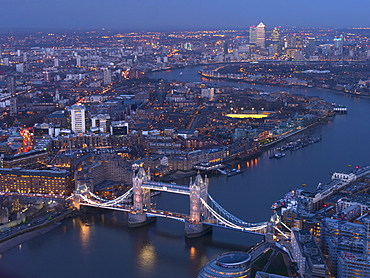 Aerial photo showing Tower Bridge, River Thames and Canary Wharf at dusk, London, England, United Kingdom, Europe