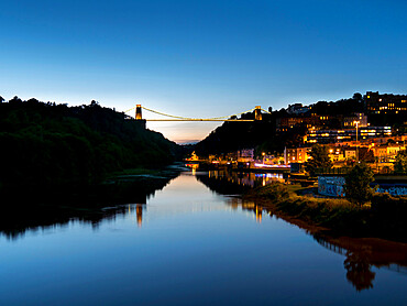 Clifton suspension bridge is reflected in River Avon at dusk