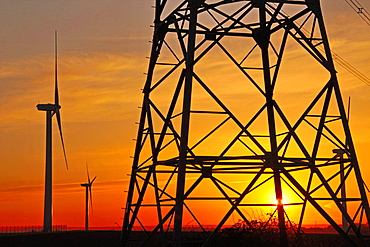 Windmills, pylon and power lines in morning light, Germany, Europe